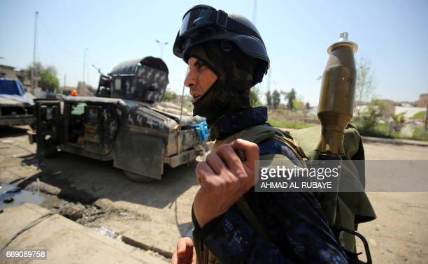 A member of the Iraqi forces carries a rocket launcher on his back as he stands past humvees in the old city of Mosul on April 16 during an offensive...