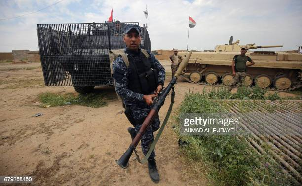 A member of the Iraqi forces carries a rocketpropelled grenade launcher during the advance towards the alHaramat neighbourhood north of Mosul on May...