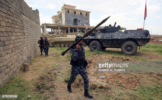 A member of the Iraqi forces carries a rocketpropelled grenade launcher as he walks during the advance towards the alHaramat neighbourhood north of...