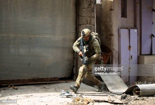 TOPSHOT A member of the Iraqi forces consisting of the Iraqi federal police and the elite Rapid Response Division runs for cover as they advance in...