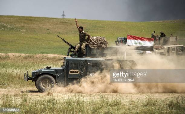 TOPSHOT A member of the Iraqi forces' Emergency Response Division rides on top of a humvee advancing on the frontlines in west Mosul on May 6 during...