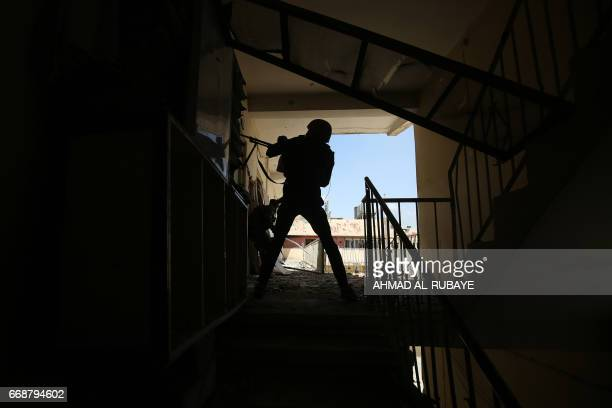 TOPSHOT A member of the Iraqi forces fires towards Islamic State group fighters in the old city of Mosul on April 15 during an offensive to recapture...