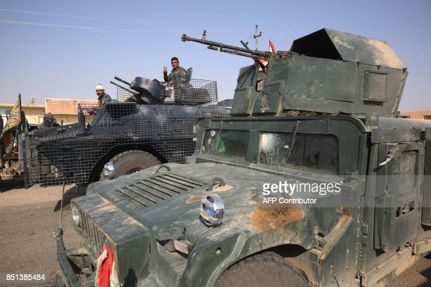 A member of the Iraqi forces flashes the victory gesture from the turret of an armoured vehicle during the advance towards the northern Iraqi town of...