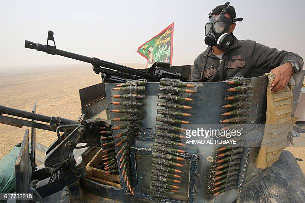 TOPSHOT A member of the Iraqi forces holds a position at the alShura area south of Mosul on October 24 during an operation to retake the main hub...