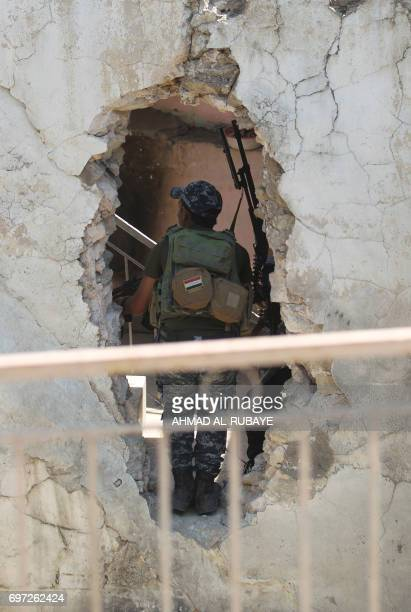 A member of the Iraqi forces is seen through a hole in the wall during their advance towards Mosul's Old City on June 18 during the ongoing offensive...