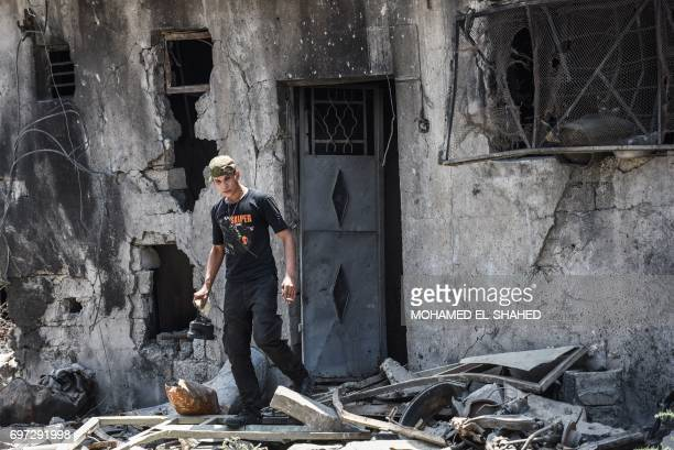A member of the Iraqi forces leaves a damaged building carrying a kettle at an army position as troops advance towards Mosul's Old City on June 18...