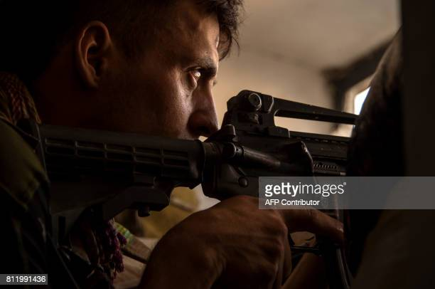 A member of the Iraqi forces looks through the sights of an M4 assault rifle during the offensive against Islamic State group fighters in the Old...