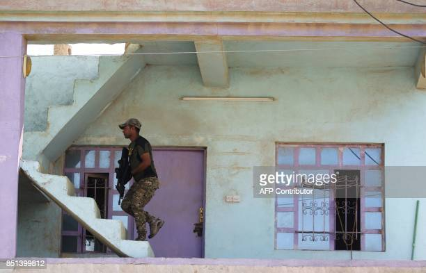 A member of the Iraqi forces patrols inside a building in the northern Iraqi town of Sharqat on September 22 during a new offensive against the...