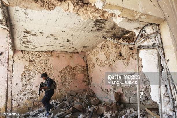 TOPSHOT A member of the Iraqi forces patrols inside a damaged building during the advance towards the Old City of Mosul on June 19 2017 as the...