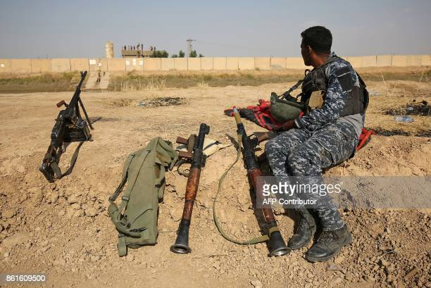 TOPSHOT A member of the Iraqi forces sits on a river bank across from Kurdish peshmerga positions on October 15 on the southern outskirts of Kirkuk...