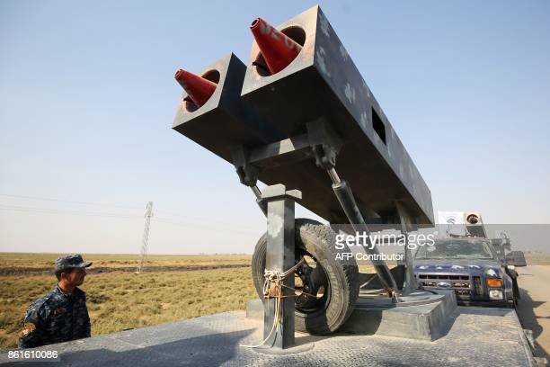 A member of the Iraqi forces stands next to a rocket launcher as an army convoy drives towards Kurdish peshmerga positions on October 15 on the...