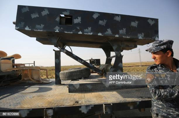 A member of the Iraqi forces stands next to a rocket launcher as they drive towards Kurdish peshmerga positions on October 15 on the southern...