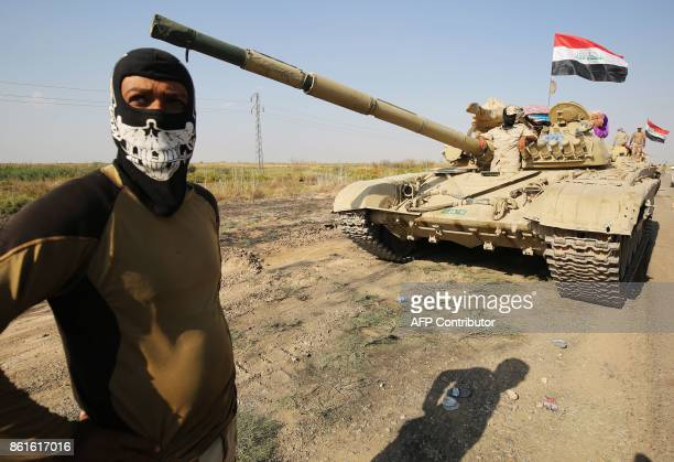 A member of the Iraqi forces stands next to a tank as an army convoy drives towards Kurdish peshmerga positions on the southern outskirts of Kirkuk...