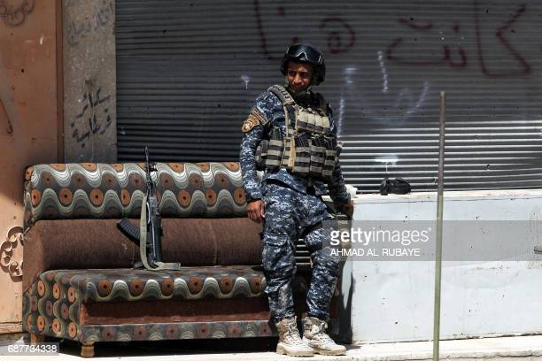 TOPSHOT A member of the Iraqi forces takes a break near the frontline in the old city of Mosul on May 24 during the ongoing offensive to retake the...