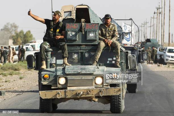 A member of the Iraqi forces uses his cellphone to take a 'selfie' photograph of himself and a comrade as they ride on a humvee during the advance...