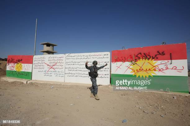 TOPSHOT A member of the Iraqi forces walks past a defaced Kurdish flag painted on concrete blocks on the outskirts of Kirkuk on October 16 as troops...