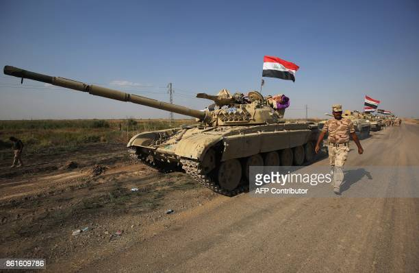 A member of the Iraqi forces walks past a tank as an army convoy drives towards Kurdish peshmerga positions on October 15 on the southern outskirts...