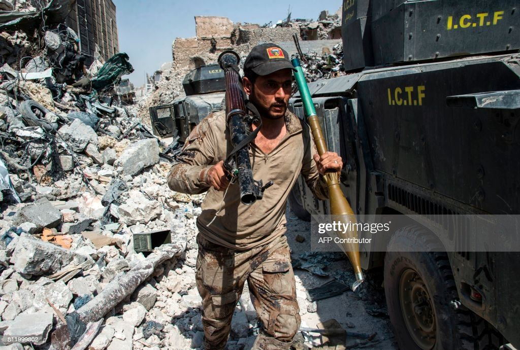 TOPSHOT - A member of the Iraqi forces walks through the rubble past humvees as he carries a rocket-propelled grenade and launcher in the Old City of Mosul on July 10, 2017, during the offensive to retake the embattled city from Islamic State (IS) group fighters. / AFP PHOTO / Fadel SENNA