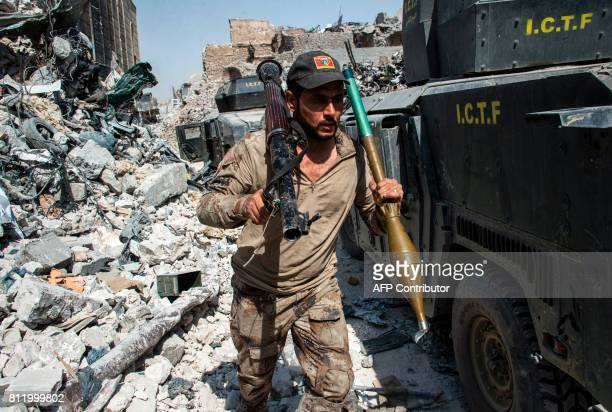 TOPSHOT A member of the Iraqi forces walks through the rubble past humvees as he carries a rocketpropelled grenade and launcher in the Old City of...