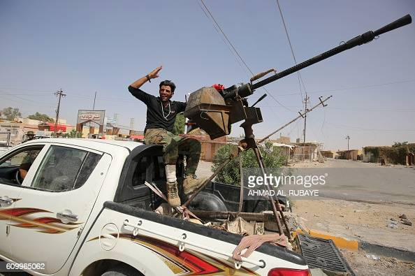 A member of the Iraqi government forces celebrates on the back of a heavily armed vehicle in the town of Sharqat around 80 kilometres south of the...