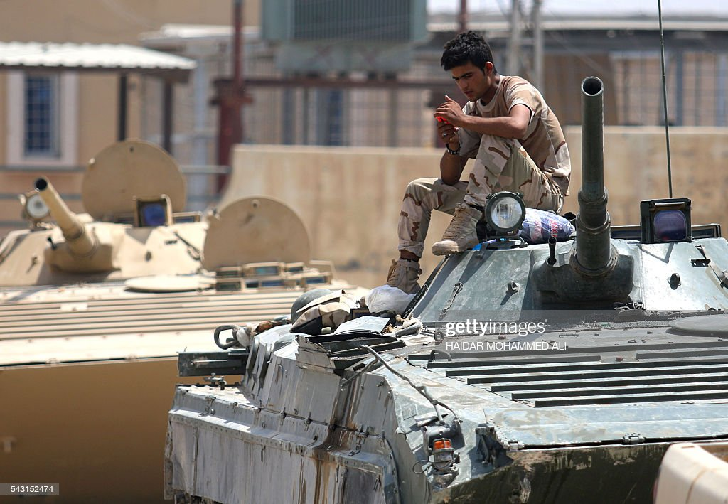 A member of the Iraqi government forces checks his mobile phone while sitting on a tank in Fallujah, 50 kilometres (30 miles) from the capital Baghdad, after forces retook the embattled city from the Islamic State group on June 26, 2016. Iraqi Prime Minister Haider al-Abadi urged all Iraqis to celebrate the recapture of Fallujah by the security forces and vowed the national flag would be raised in Mosul soon. While the battle has been won, Iraq still faces a major humanitarian crisis in its aftermath, with tens of thousands of people who fled the fighting desperately in need of assistance in the searing summer heat. ALI