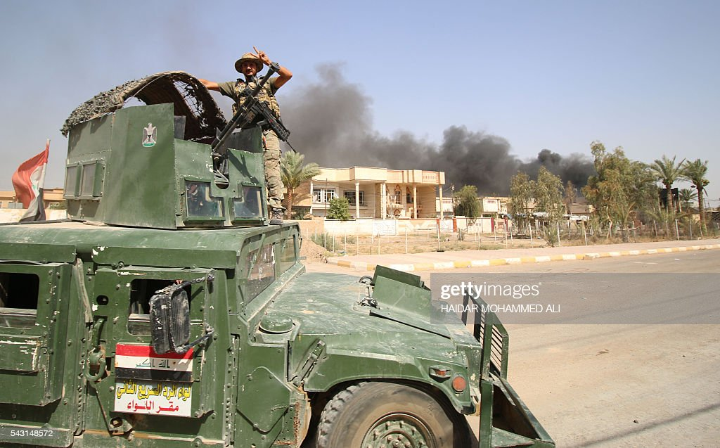 A member of the Iraqi government forces flashes the 'V' for victory sign as smoke billows in the background in Fallujah, 50 kilometres (30 miles) from the capital Baghdad, after forces retook the embattled city from the Islamic State group on June 26, 2016. Iraqi Prime Minister Haider al-Abadi urged all Iraqis to celebrate the recapture of Fallujah by the security forces and vowed the national flag would be raised in Mosul soon. While the battle has been won, Iraq still faces a major humanitarian crisis in its aftermath, with tens of thousands of people who fled the fighting desperately in need of assistance in the searing summer heat. ALI