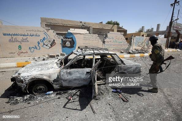 A member of the Iraqi government forces looks at a burntout vehicle as they secure the town of Sharqat around 80 kilometres south of the city of...