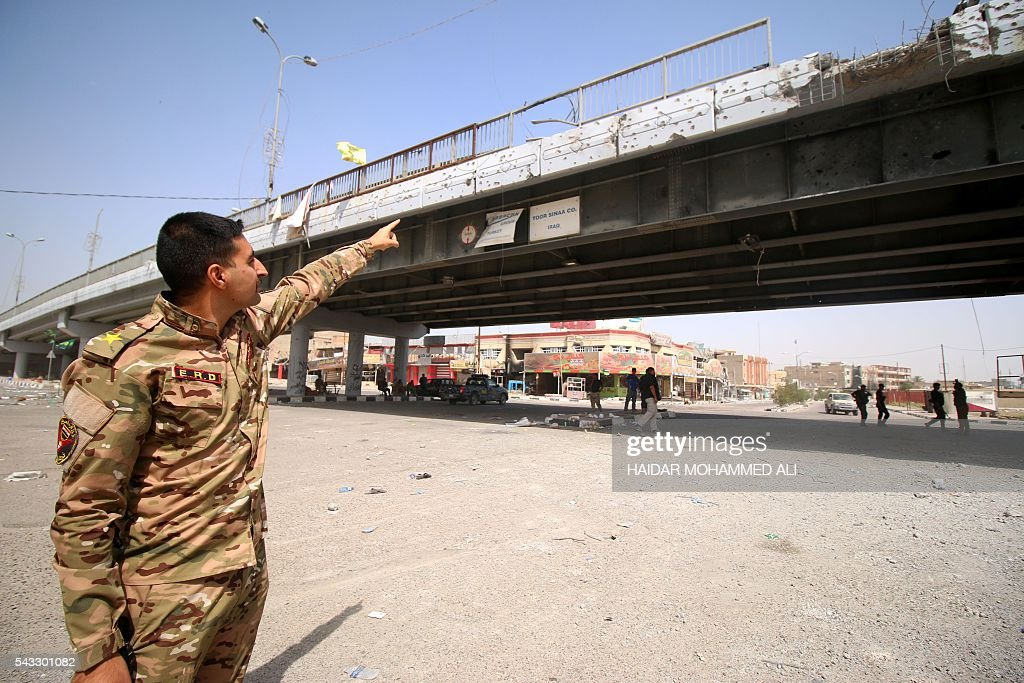 A member of the Iraqi government forces points at a bridge on June 27, 2016 in western Fallujah, 50 kilometres (30 miles) from the Iraqi capital Baghdad, after Iraqi forces retook the embattled city from the Islamic State group. Iraqi forces took the Islamic State group's last positions in the city of Fallujah on June 26, 2016, establishing full control over one of the jihadists' most emblematic bastions after a month-long operation. ALI
