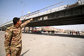 A member of the Iraqi government forces points at a bridge on June 27 2016 in western Fallujah 50 kilometres from the Iraqi capital Baghdad after...
