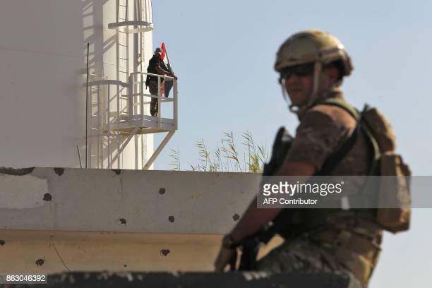 A member of the Iraqi government forces stands guard in a humvee turret as another raises the Iraqi national flag from an oil silo at the Bai Hassan...