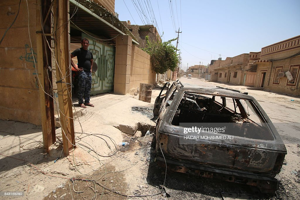 A member of the Iraqi government forces stands near a charred car in Fallujah, 50 kilometres (30 miles) from the capital Baghdad, after they retook the embattled city from the Islamic State group on June 26, 2016. Iraqi Prime Minister Haider al-Abadi urged all Iraqis to celebrate the recapture of Fallujah by the security forces and vowed the national flag would be raised in Mosul soon. While the battle has been won, Iraq still faces a major humanitarian crisis in its aftermath, with tens of thousands of people who fled the fighting desperately in need of assistance in the searing summer heat. ALI