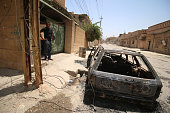 A member of the Iraqi government forces stands near a charred car in Fallujah 50 kilometres from the capital Baghdad after they retook the embattled...