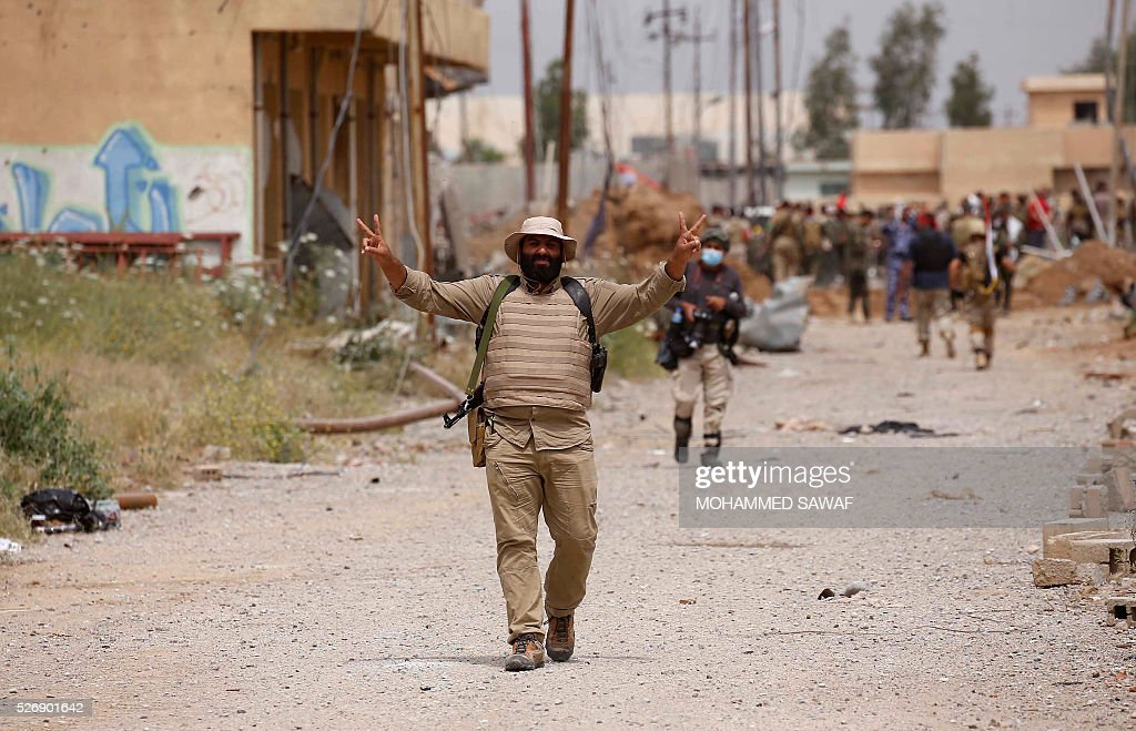 A member of the Iraqi Kurdish forces flashes the sign for victory as he walks in the northern Iraqi town of Bashir after recapturing the town from the Islamic State (IS) group on May 1, 2016. Pressure for an operation to retake the town had grown in March after IS launched a chemical attack from Bashir on the nearby town of Taza that killed at least three children. / AFP / Mohammed SAWAF