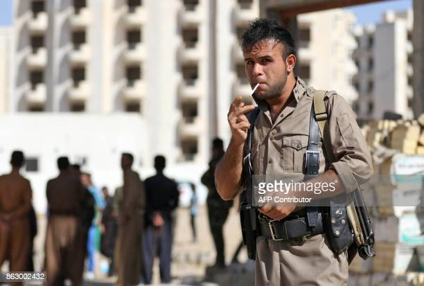 A member of the Iraqi Kurdish forces stands guard at an unfinished housing project where displaced people fleeing violence in the northern Kirkuk...
