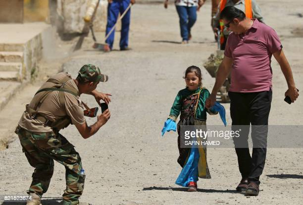 A member of the Iraqi Kurdish security forces takes a picture of a Christian girl as she arrives for a mass at the Church of the Immaculate...