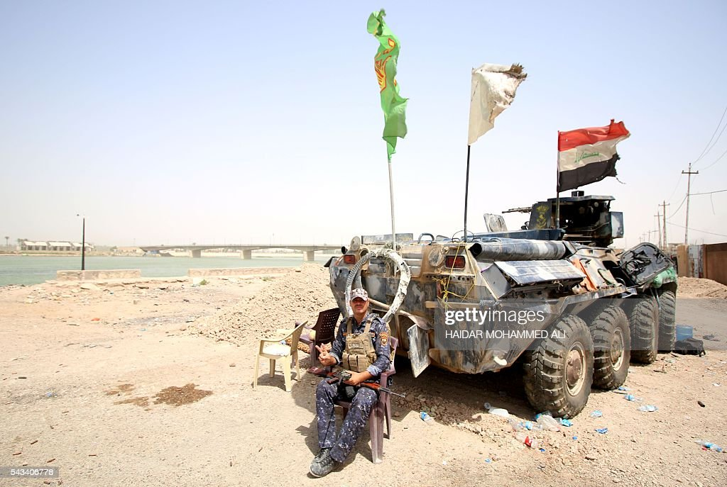 A member of the Iraqi police sits next to an armoured vehicle in Fallujah on June 28, 2016, after Iraqi forces retook the city from the Islamic State group. Iraqi forces took the Islamic State group's last positions in Fallujah on June 26, 2016, establishing full control over one of the jihadists' most emblematic bastions after a month-long operation. / AFP / HAIDAR