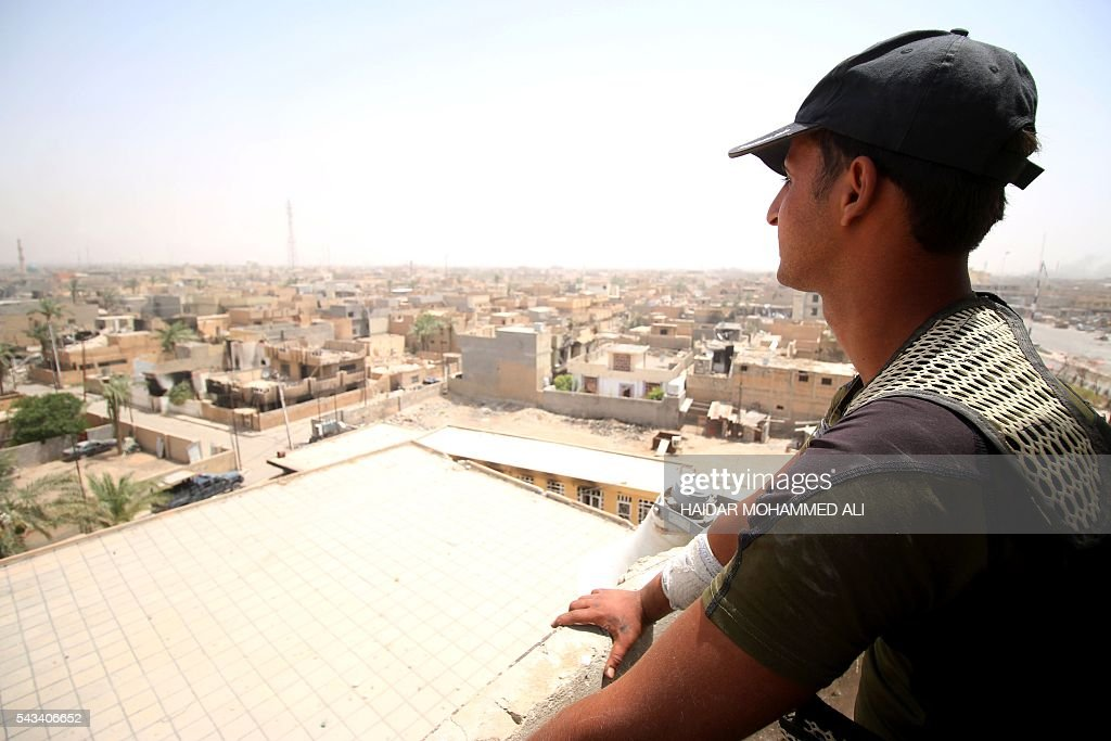 A member of the Iraqi police stands on a roof overlooking Fallujah on June 28, 2016, after Iraqi forces retook the city from the Islamic State group. Iraqi forces took the Islamic State group's last positions in Fallujah on June 26, 2016, establishing full control over one of the jihadists' most emblematic bastions after a month-long operation. / AFP / HAIDAR