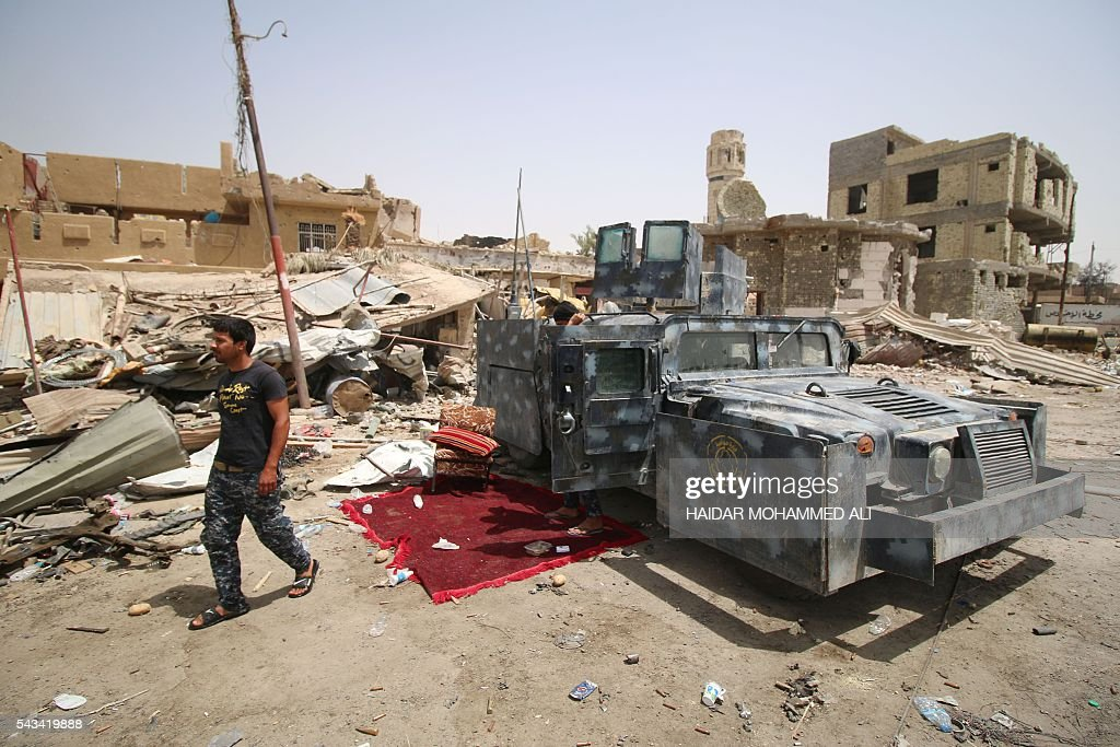 A member of the Iraqi police walks past an armoured vehicle parked next to destroyed buildings in Fallujah on June 28, 2016, after Iraqi forces retook the city from the Islamic State group. Iraqi forces took the Islamic State group's last positions in Fallujah on June 26, 2016, establishing full control over one of the jihadists' most emblematic bastions after a month-long operation. / AFP / HAIDAR