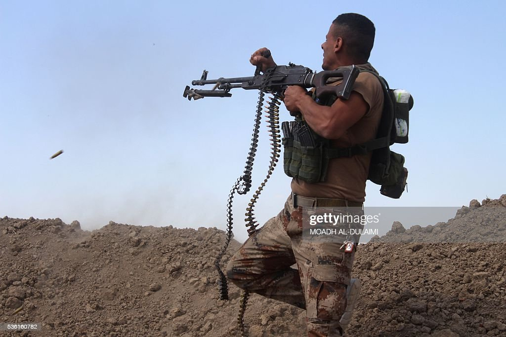 A member of the Iraqi pro-governement forces fires his weapon on a front line in the Albu Huwa area, south of Fallujah near the Euphrates river, on May 31, 2016, during an operation aimed at retaking areas from the Islamic State group. Iraqi forces launched an offensive a week ago to recapture Fallujah, which became an IS group stronghold after its fighters seized the city in January 2014. / AFP / MOADH