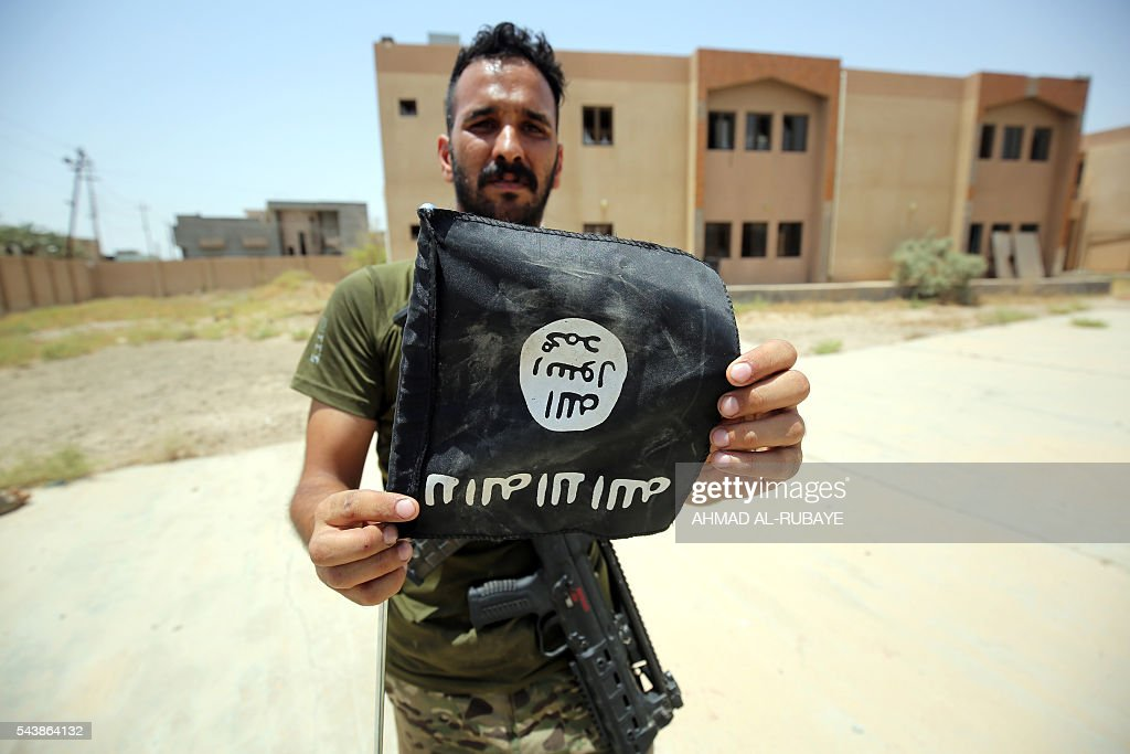A member of the Iraqi police forces holds an upside down Islamic State (IS) group flag in a street in Fallujah on June 30, 2016 after recapturing the city from the jihadists. Iraqi forces have retaken full control of Fallujah, a longtime jihadist bastion just 50 kilometres (30 miles) west of Baghdad, after a vast operation that was launched in May. / AFP / AHMAD