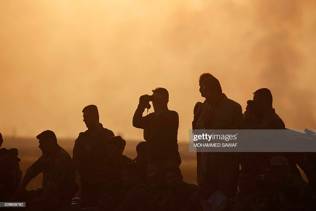 A member of the Iraqi pro-government forces uses binoculars during an operation to retake the town of al-Bashir, near Kirkuk, from the Islamic State group (IS), on April 30, 2016. Iraqi forces launched a final assault Saturday to retake the Turkmen majority town of Bashir from the Islamic State jihadist group, Kurdish authorities said. 'Bashir village is surrounded and 80 percent has been cleared,' the Kurdistan Region Security Council said on social media. Turkmen units from Iraq's Hashed al-Shaabi (Popular Mobilisation) militia umbrella group, which announced an operation to retake the town earlier this month, were also taking part. / AFP / Mohammed SAWAF