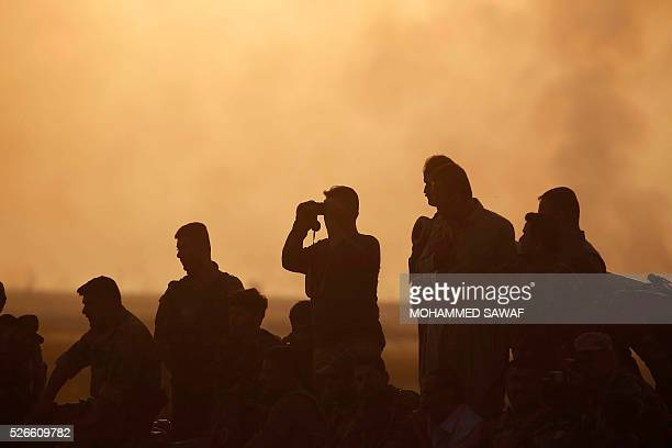 TOPSHOT A member of the Iraqi progovernment forces uses binoculars during an operation to retake the town of alBashir near Kirkuk from the Islamic...