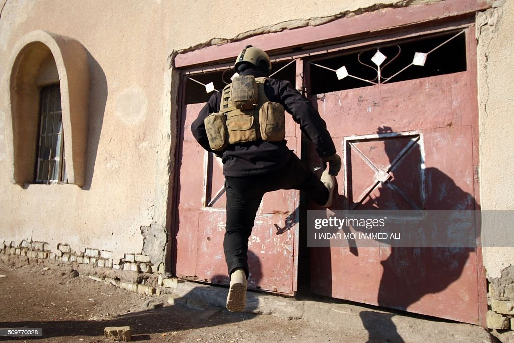 A member of the Iraqi security forces breaks down a door in the Nahr al-Ezz area, 150km North of Basra, on February 12, 2016 during a security operation. Operations by the security forces, including the intelligence services, are regular in the area in an attempt to contain and disarm feuding local gangs and tribes. / AFP / HAIDAR MOHAMMED ALI