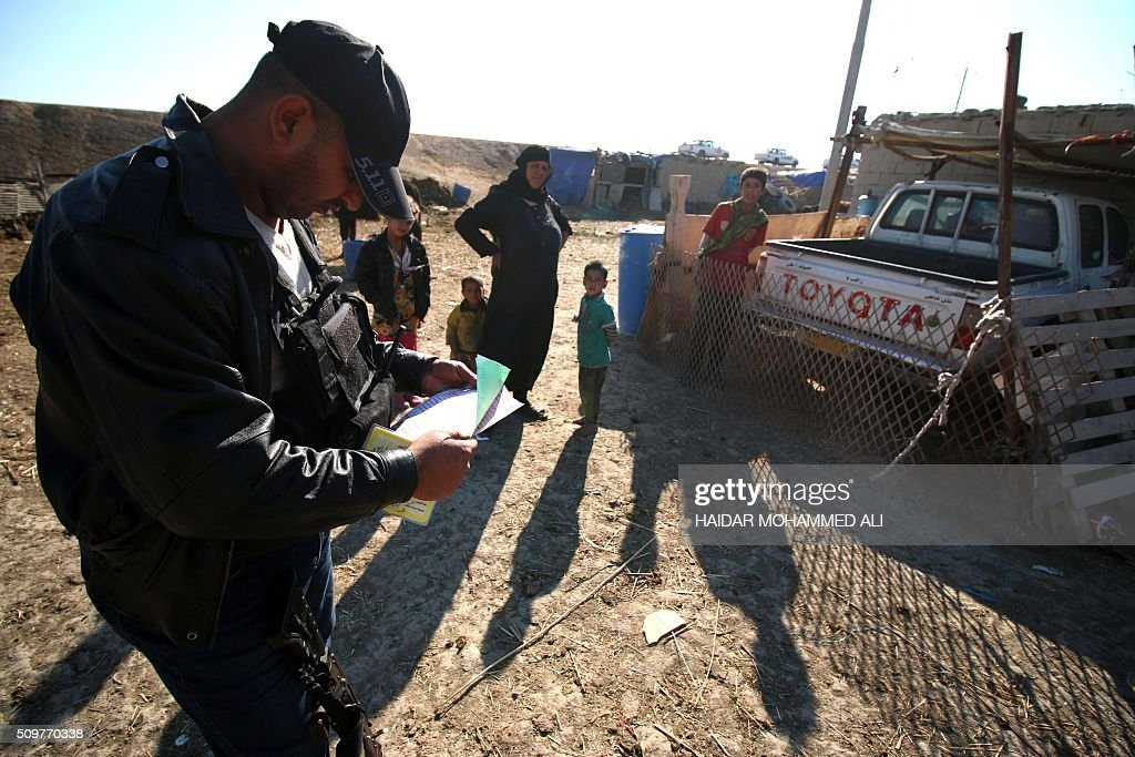 A member of the Iraqi security forces checks the papers of civilians in the Nahr al-Ezz area, 150km North of Basra, on February 12, 2016 during a security operation. Operations by the security forces, including the intelligence services, are regular in the area in an attempt to contain and disarm feuding local gangs and tribes. / AFP / HAIDAR MOHAMMED ALI
