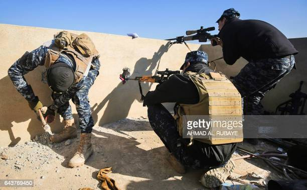 TOPSHOT A member of the Iraqi security forces creates holes in a wall for snipers as two others take position in the village of alBuseif south of...