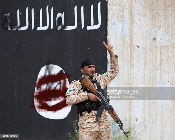 A member of the Iraqi security forces flashes the sign for victory in front of a defaced Islamist flag in Tikrit on April 1 a day after the Iraqi...