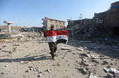 TOPSHOT A member of the Iraqi security forces holds his national flag on December 28 2015 at the heavily damaged government complex after they...
