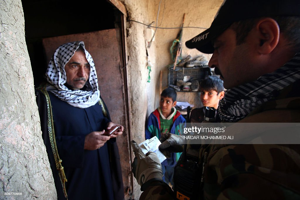 A member of the Iraqi security forces inspects the ID of a man in the Nahr al-Ezz area, 150km North of Basra, on February 12, 2016 during a security operation. Operations by the security forces, including the intelligence services, are regular in the area in an attempt to contain and disarm feuding local gangs and tribes. / AFP / HAIDAR MOHAMMED ALI