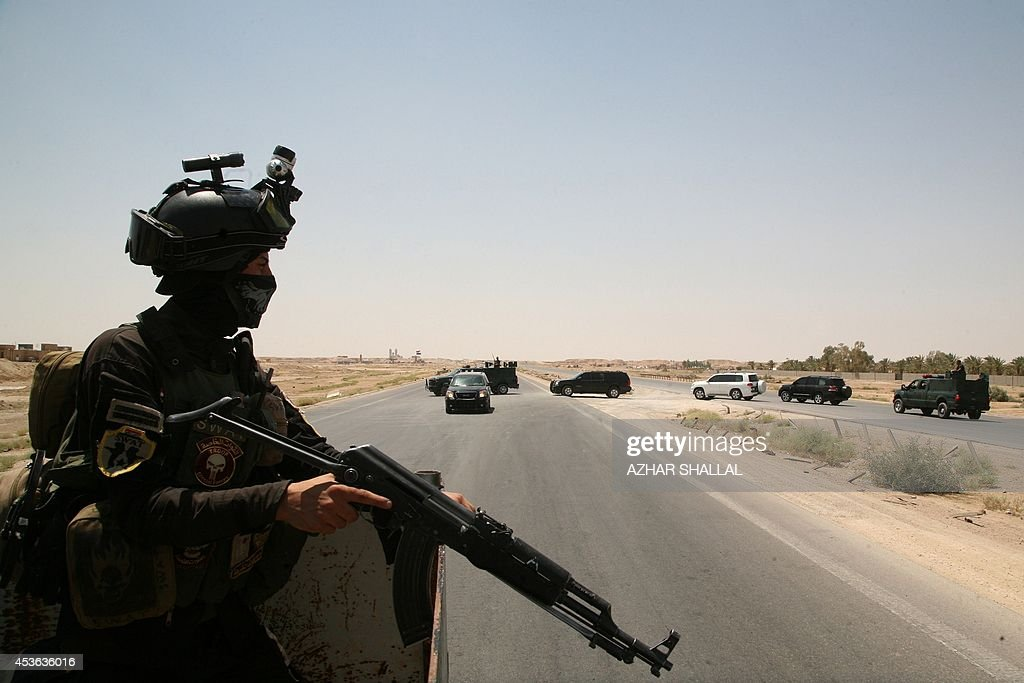 A member of the Iraqi security forces keeps watch on August 14 2014 on the main highway near Ramadi Anbar's provincial capital west of Baghdad which...
