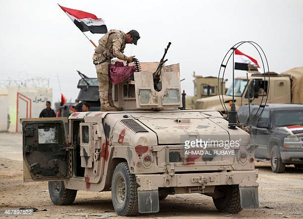 A member of the Iraqi security forces stands atop a military vehicle outside the western entrance of the city of Tikrit on March 28 2015 during a...